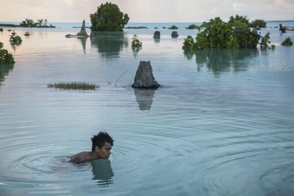 Sixteen-year-old Peia Kararaua swims in a flooded neighbourhood in the village of Aberao on the Kiribati islands.