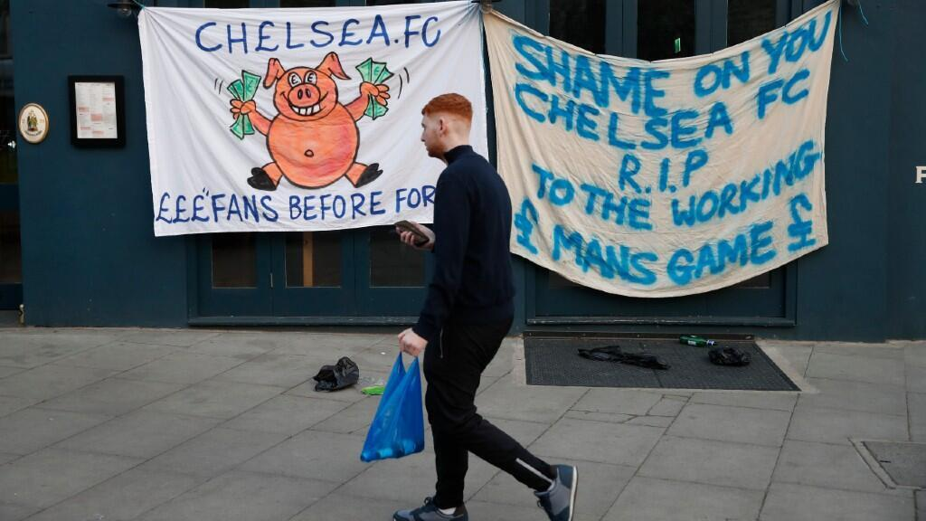 A Chelsea fan walks past the banners outside the stadium before the game and after reports surfaced suggesting a possible withdrawal of the club from the Super League.  London, UK, April 20, 2021.