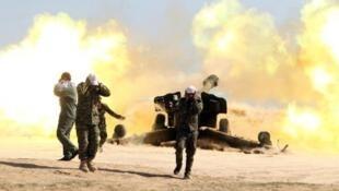 مقاتلون شيعة يشاركون في قصف بلدة قريبة من تكريت خلال عمليات الجيش العراقي ضد تنظيم الدولة الإسلامية