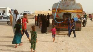Des déplacés de la ville irakienne de Falloujah patientent pour recevoir de l'eau et des vivres dans un camp près de Ramadi le 18 juin 2016.