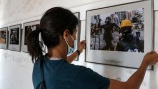 """Una trabajadora cuelga fotos para la exposición """"Opposing Views"""" del fotoperiodista británico de la AFP Anthony Wallace, con motivo de la 32ª edición del festival internacional """"Visa pour l'Image"""" de Perpiñán, Francia, el 25 de agosto de 2020"""
