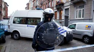 Un policier est posté le 19 mars 2016 dans le périmètre de sécurité entourant le lieu où ont été arrêtés cinq personnes dont Salah Abdeslam.