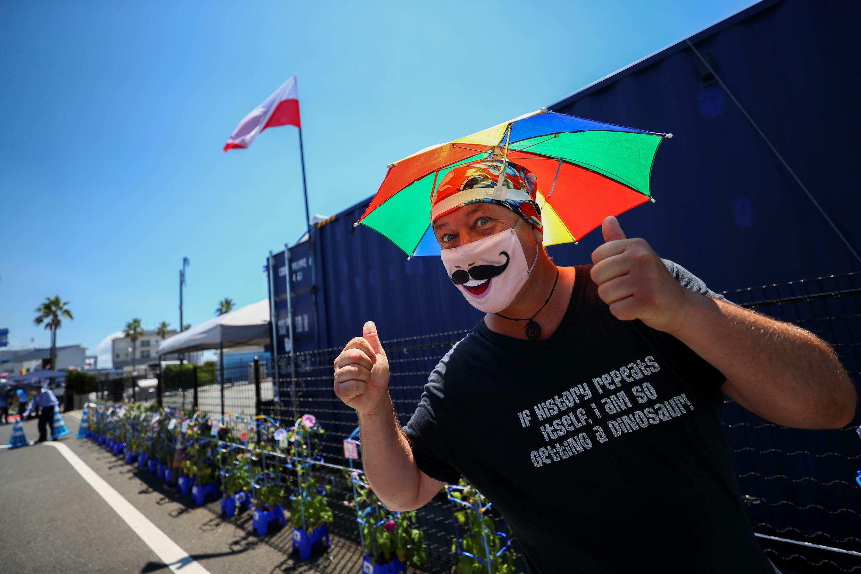 A man wearing a protective face mask puts up his thumbs at the Tokyo 2020 Olympic Games sailing venue in Enoshima Yacht Harbor, Fujisawa City, Japan, July 22, 2021.
