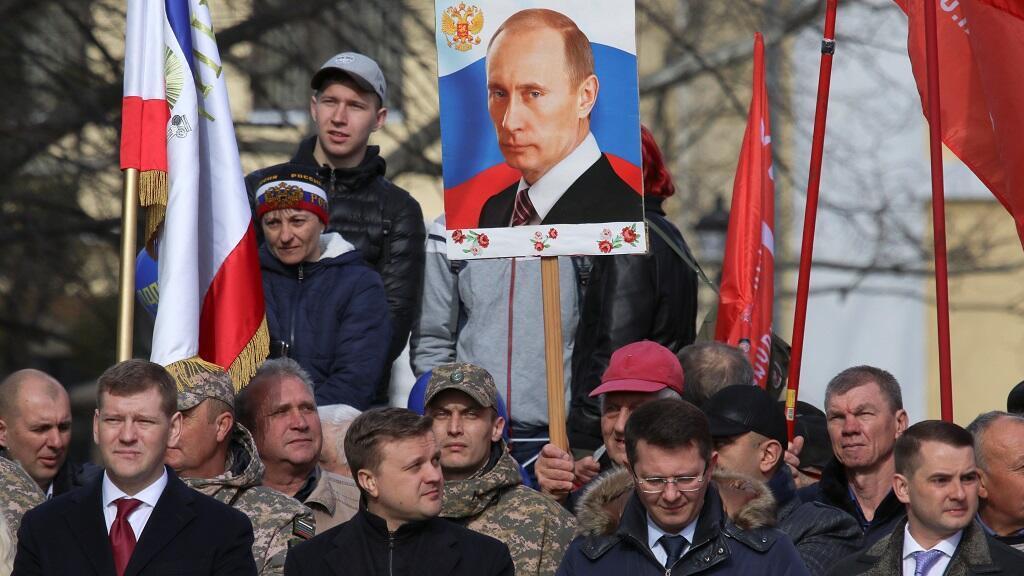 Un hombre sostiene un tablero con un retrato del presidente ruso Vladimir Putin durante las celebraciones del quinto aniversario de la anexión de Crimea por parte de Rusia en Simferopol, el 15 de marzo de 2019.