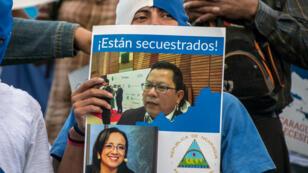 """Un nicaragüense tiene una pancarta con los retratos de los periodistas Miguel Mora (arriba) y Lucía Pineda (abajo) con una leyenda que dice """"Están secuestrados"""", durante una manifestación frente a la embajada de Nicaragua en San José, Costa Rica, el 22 de diciembre de 2018."""