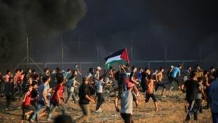 فلسطينيون يركضون أثناء مواجهات قرب السياج الفاصل مع إسرائيل في قطاع غزة الجمعة في 21 أيلول/سبتمبر 2018