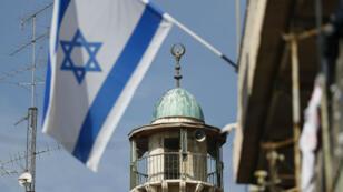 Un drapeau israélien flotte devant le minaret d'une mosquée du quartier arabe de la vieille ville de Jérusalem, le 14 novembre 2016.