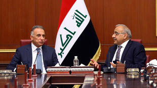 Iraqi Prime Minister Mustafa Kadhemi (L) sits next to outgoing premier Adel Abdel Mahdi during a meeting with members of the new government in Baghdad on May 7, 2020