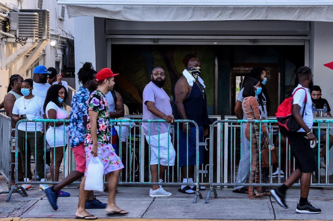 Un grupo de personas hace fila para ingresar a un restaurante en Ocean Drive en Miami Beach, Florida, el 26 de junio de 2020.