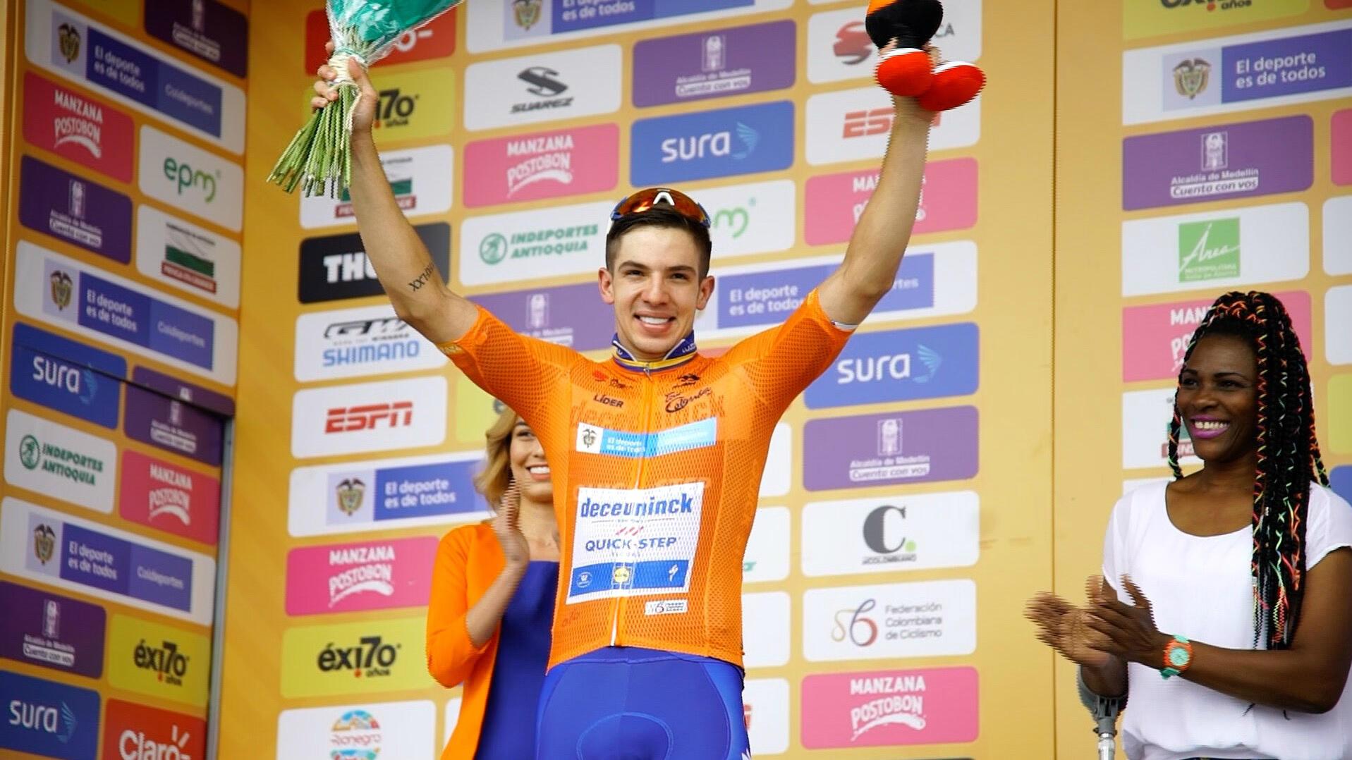 Álvaro Hodeg (Deceuninck-Quick Step) celebra su triunfo en la segunda etapa y porta la camiseta naranja que lo acredita como nuevo líder del Tour Colombia 2.1, en La Ceja, Colombia, el 13 de febrero de 2019.