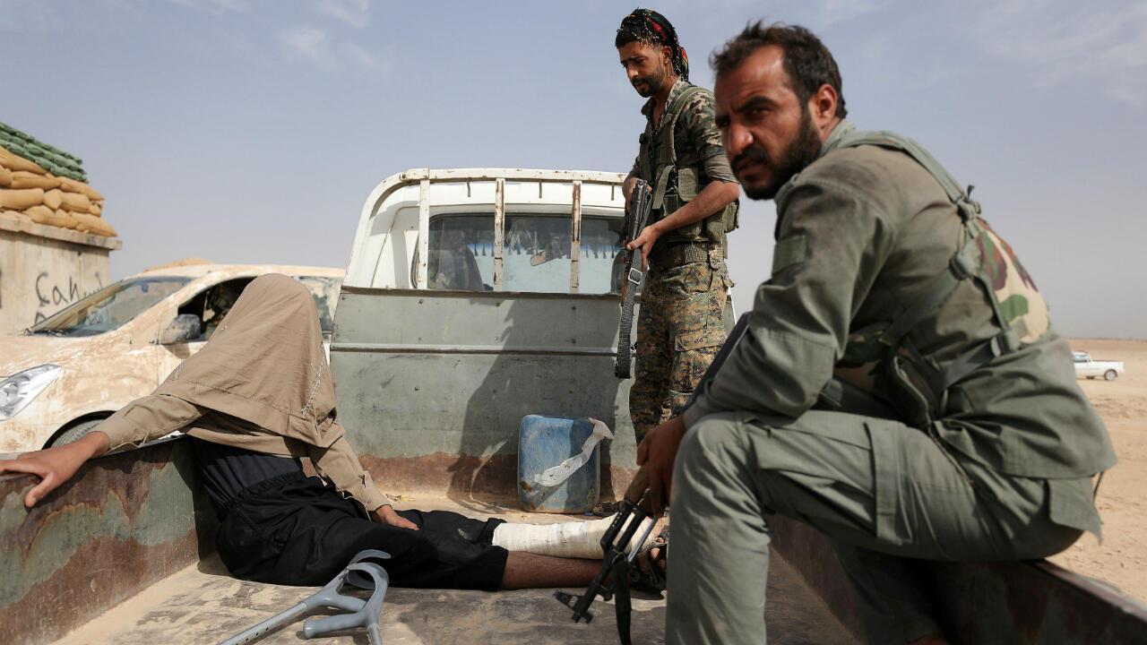 Foto de archivo en la que se ve a combatientes de las Fuerzas Democráticas Sirias (FDS) después de arrestar a un hombre herido durante su lucha con el Estado Islámico en la zona norte de Deir al-Zor, Siria, el 24 de septiembre de 2017.