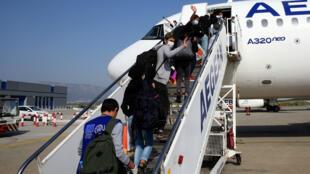Un grupo de refugiados menores de edad no acompañados, hasta ahora recluidos en campamentos superpoblados en el mar Egeo abordan un vuelo en el Aeropuerto Internacional de Atenas, Grecia, para ser trasladados a Luxemburgo. el 15 de abril. 2020.