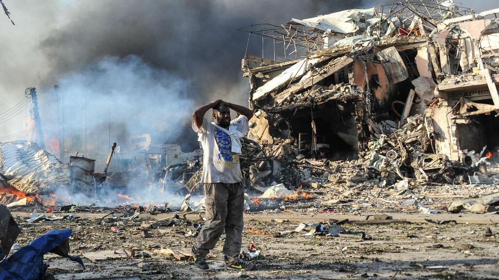 Ante el atentado, un hombre somalí reacciona junto a un cadáver en el sitio donde explotó un carro bomba en el centro de Mogadiscio el 14 de octubre.