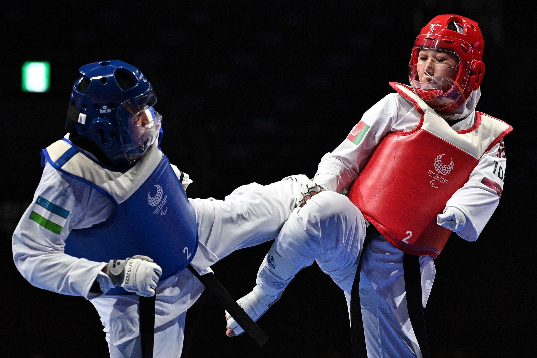 Zakia Khudadadi (en rouge) face à l'Ouzbèque Ziyodakhon Isakova, lors de leur match de taekwondo féminin K44, à Tokyo le 2 septembre 2021.