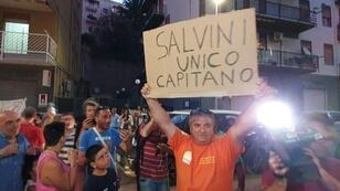 """A man holds a placard reading """"Salvini is the only captain"""""""