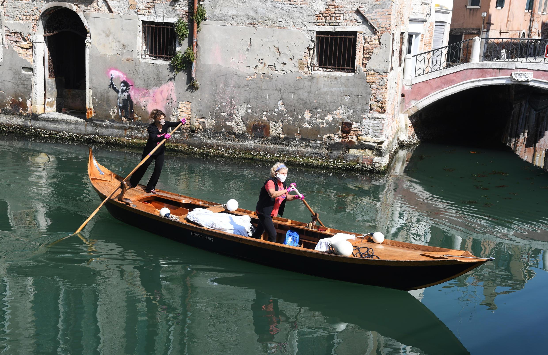 Dos mujeres de una ONG dedicada a preservar las góndolas pasan junto a una pbra de Banksy al repartir comida entre las familias que no tienen la posibilidad de salir a comprarla el 18 de abril de 2020 en Venecia, Italia.