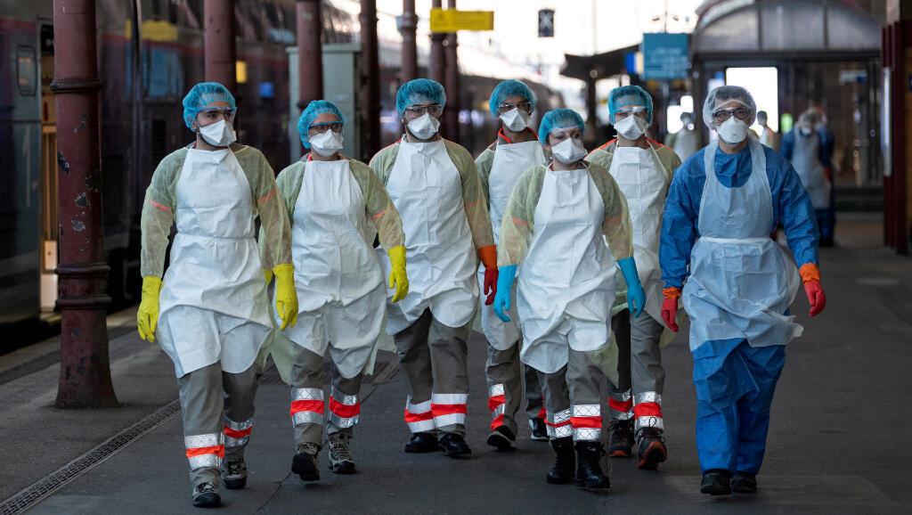 Estos profesionales de la salud están el 3 de abril en Estrasburgo, Francia, para remitir un paciente de Covid-19 en un tren medicalizado.