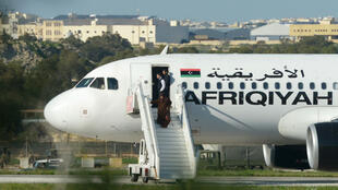 Des passagers sortent de l'avion de la compagnie libyenne Afriqiyah Airways détourné vendredi 23 décembre.