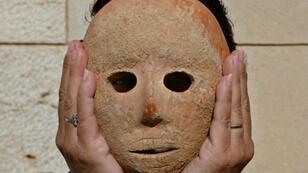 Israeli archeologist Ronit Lupu holds a rare stone mask dating to the Neolithic period which was found at the Pnei Hever region of southern Hebron mount, in this picture taken on November 28, 2018