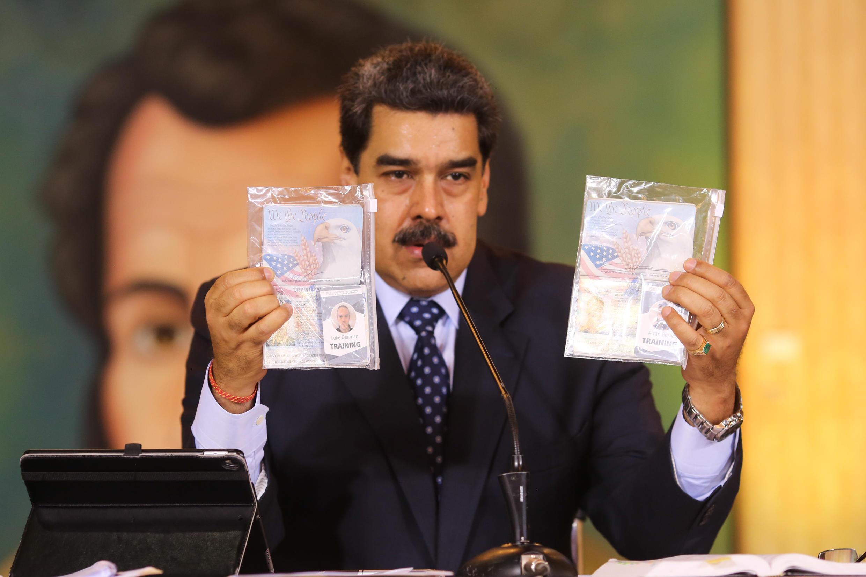 El presidente venezolanos, Nicolás Maduro, mientras muestra los pasaportes de dos ciudadanos estadounidenses arrestados por las fuerzas de seguridad en el Palacio de Miraflores, en Caracas, el 6 de mayo de 2020.