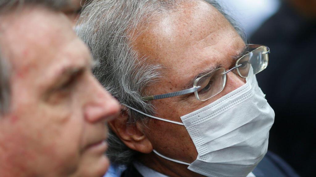 El ministro de Economía de Brasil, Paulo Guedes, con una máscara protectora observa junto al presidente, Jair Bolsonaro, durante una conferencia de prensa después de una reunión con el presidente del Tribunal Federal Supremo de Brasil, Dias Toffoli, en medio del brote de Covid-19, en el Tribunal Federal Supremo, en Brasilia, Brasil, el 7 de mayo de 2020.