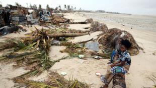 Los niños se sientan entre los desechos de la tormenta que quedaron después del ciclón Idai, en Beira, la ciudad más afectada de Mozambique, el 23 de marzo de 2019.