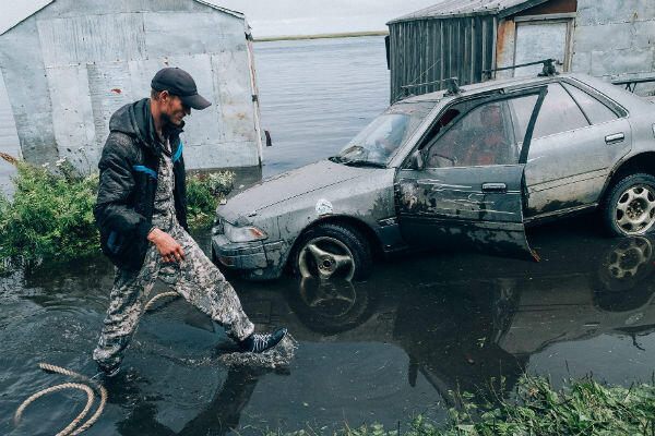 Sergey tries to get his car out of a flooded neighbourhood in Oktyabrsky, Russia.