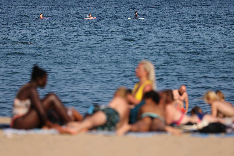 La gente disfruta del clima soleado en la playa, luego de que España reabriera oficialmente las fronteras en medio del brote de la enfermedad del coronavirus, en Barcelona, España, el 21 de junio de 2020.