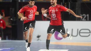 لاعب المنتخب المصري يحيى الدرع (يمين) يحتفل بهزه شباك تشيلي في المباراة الافتتاحية لكأس العالم في كرة اليد في القاهرة في 13 كانون الثاني/يناير 2021.