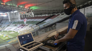 Fluminense DJ Franklin Scheleger, 29, plays sounds and songs miming a crowded stadium, during the Brazilian Championship match between Fluminense and Atletico Goianiense at the Maracana stadium in Rio de Janeiro, Brazi