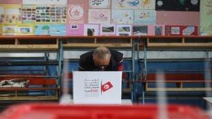 رجل يستعد لفرز الأصوات في مركز اقتراع خلال الدورة الثانية للانتخابات الرئاسية في تونس، 13 أكتوبر/ تشرين الأول 2019.