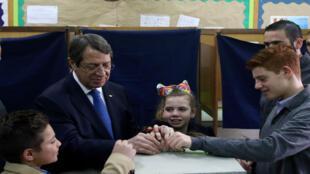 Presidente Nicos Anastasiades vota con la ayuda de sus nietos en Limassol, Chipre, el 4 de febrero de 2018.