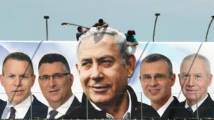 Trabajadores levantan un cartel del primer ministro israelí, Benjamin Netanyahu, quien figura en la imagen junto a los candidatos de su partido. Jerusalén, el 28 de marzo de 2019.