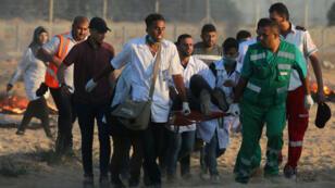 Des secouristes palestiniens venant en aide à un manifestant blessé vendredi 3 août à la frontière entre Gaza et Israël.