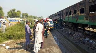 Rescue workers gather beside the burnt-out train carriages after a passenger train caught on fire near Rahim Yar Khan in Punjab province on October 31, 2019.