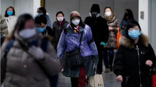 People wearing face masks walk inside a subway station, as the country is hit by an outbreak of the novel coronavirus, in Shanghai, China February 17, 2020.
