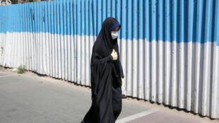 Una iraní con mascarilla camina por una calle de Teherán el 22 d ejulio de 2020