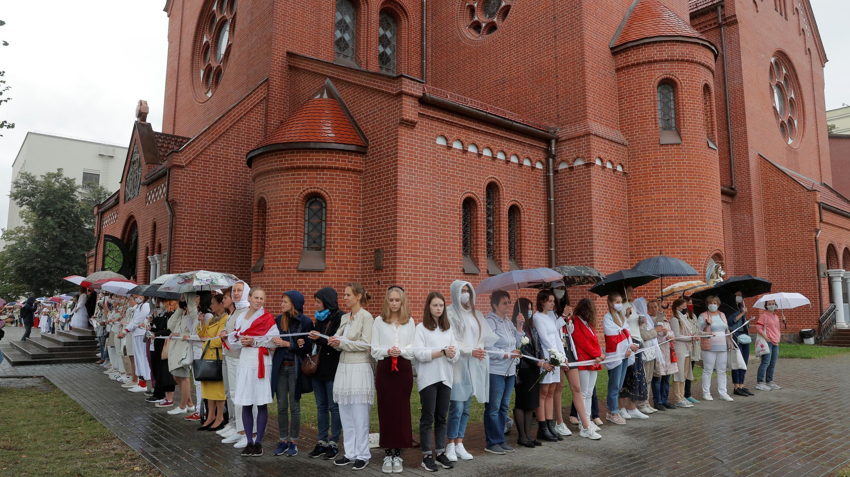 Las mujeres forman una cadena humana frente a la Iglesia de los Santos Simón y Elena durante un mitin contra los resultados de las elecciones presidenciales, en la Plaza de la Independencia en Minsk, Bielorrusia el 27 de agosto de 2020.
