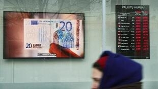 A euro bank note is screened in the window of a bank in Lithuanian capital Vilnius on December 27.