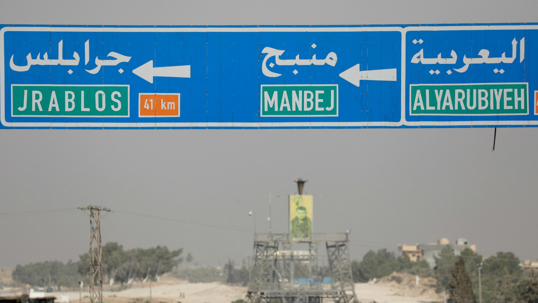 Una señal de carretera que muestra la dirección a la entrada de la ciudad de Manbij, Siria, el 15 de octubre de 2019.