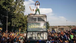 South Africa captain Siya Kolisi (C) holds the Rugby World Cup trophy during a victory parade through Soweto