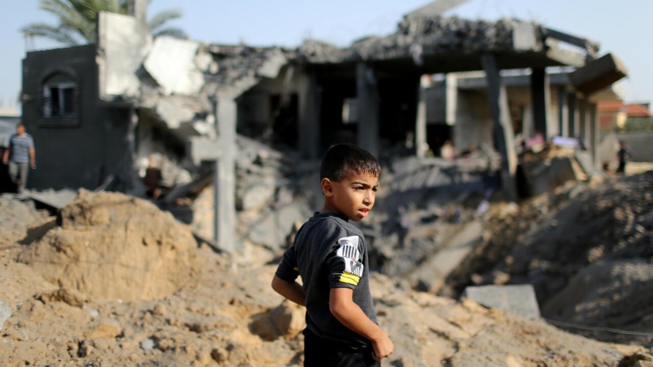 Un niño palestino observa mientras se para frente a los restos de una casa destruida en un ataque aéreo israelí en el sur de la Franja de Gaza el 13 de noviembre de 2019.