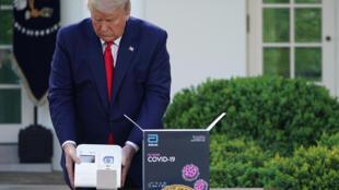 Donald Trump presenta la prueba ID NOW del grupo Abbott en la Casa Blanca el 30 de marzo de 2020