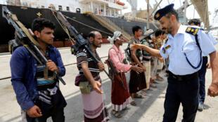 El oficial de la guardia costera yemení saluda a los miembros del movimiento hutí durante la retirada del puerto de Saleef en la provincia de Hodeida, Yemen el 11 de mayo de 2019.