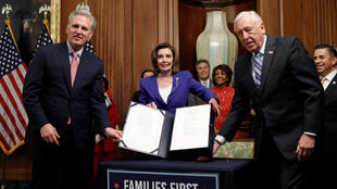 US House Speaker Nancy Pelosi is flanked by House Minority Leader Kevin McCarthy and Majority Leader Steny Hoyer as she displays the $2.2 trillion coronavirus aid bill at the US Capitol in Washington, D.C., USA, March 27, 2020.