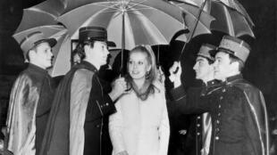 """Catherine Deneuve lors de la présentation du film """"Les parapluies de Cherbourg"""" à New York. la musique est signée Michel Legrand."""