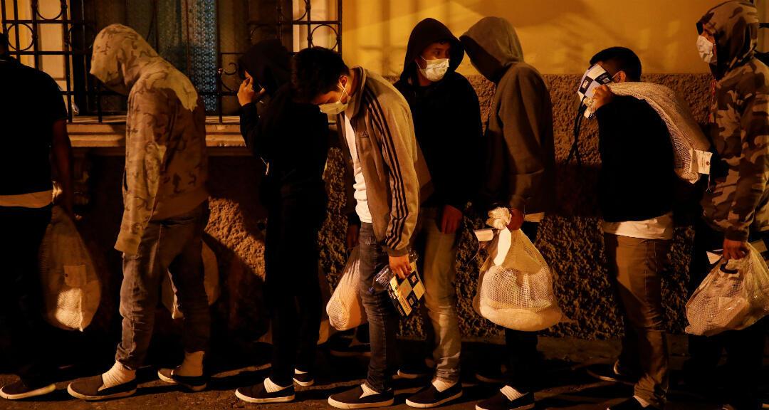 Migrantes guatemaltecos hacen fila para entrar en un hotel después de haber sido deportados de EE. UU., Ciudad de Guatemala, el 30 de abril de 2020.