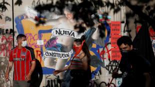 """Manifestantes caminan delante de un graffiti que dice """"Nueva Constitución"""", durante una protesta contra el Gobierno chileno en Santiago, Chile, el 5 de noviembre de 2019."""