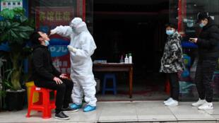 صف انتظار للخضوع لفحص لكشف الإصابة بفيروس كورونا المستجدّ في ووهان عاصمة ولاية هوباي الصينية في 29 آذار/مارس 2020