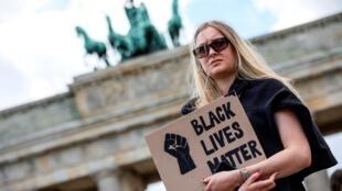 """Un contramanifestante sostiene una pancarta que dice """"Las vidas negras importan"""" cerca de una manifestación de extrema derecha ante la Puerta de Brandenburgo en Berlín, Alemania, el 6 de junio de 2020."""